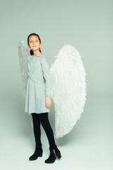 Portrait hopeful, ambitious girl wearing angel wings