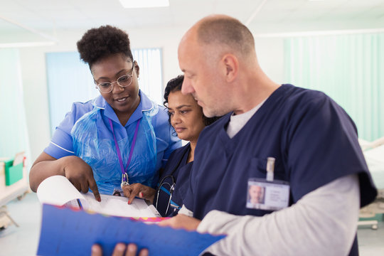 Doctors and nurse with medical chart making rounds, consulting in hospital room
