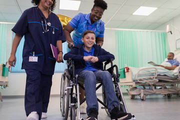 Doctor and nurse pushing boy patient in wheelchair in hospital ward