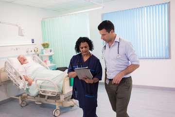 Doctors with digital tablet making rounds, consulting in hospital room