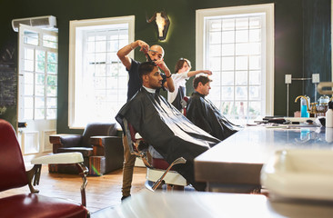 Male barber cutting hair of customer in barbershop