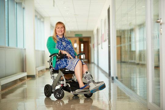 Portrait smiling woman wearing medical boot in wheelchair in corridor