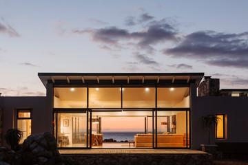 Illuminated luxury home under sky at dusk