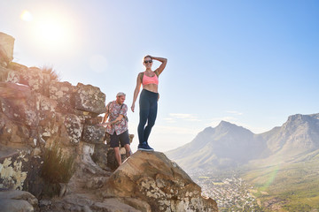 Portrait happy young woman hiking sunny cliff Cape Town South Africa Wall mural