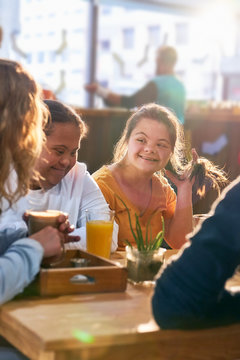 Young women with Down Syndrome talking in cafe