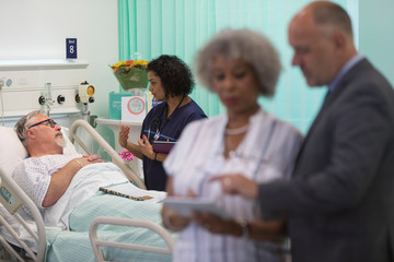 Doctor making rounds, talking with senior patient in hospital room
