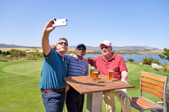 Male friends drinking beer and taking selfie on golf course patio