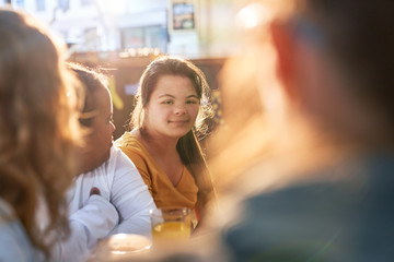 Portrait smiling young woman with Down Syndrome in cafe with friends