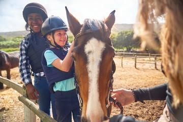 Happy girls learning horseback riding in sunny paddock