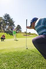 Male golfer preparing to take shot on sunny putting green