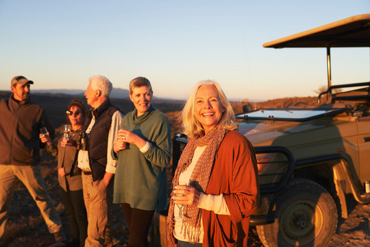 Portrait happy senior woman on safari drinking champagne with friends