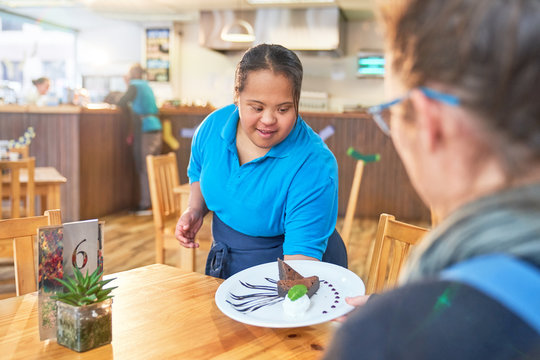 Young woman with Down Syndrome serving dessert in cafe
