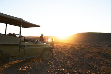 Safari tour group watching sunset by off-road vehicle South Africa