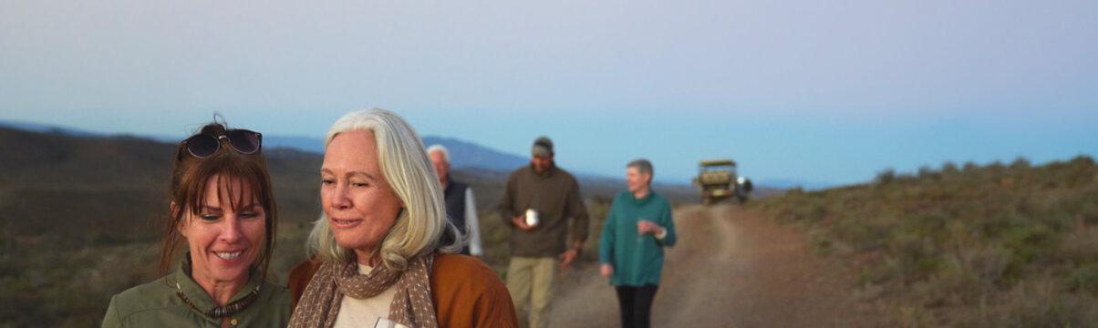 Happy women friends on safari walking on dirt road