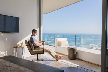 Man using digital tablet overlooking sunny ocean view
