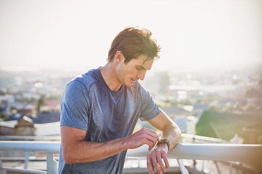 Sweaty male runner resting checking smart watch fitness tracker at sunny urban railing
