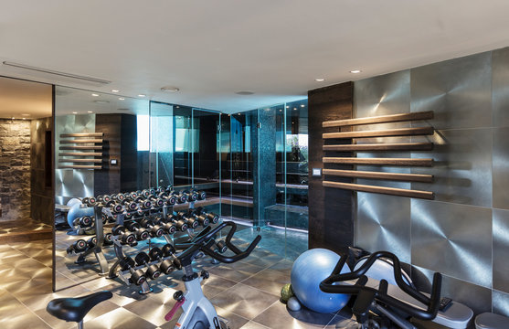 Gym with equipment in modern luxury home showcase interior