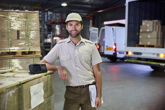 Portrait confident truck driver worker at distribution warehouse loading dock