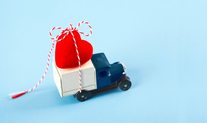 Little car carries a red heart. Concept of Valentine Day. Valentine's Day card