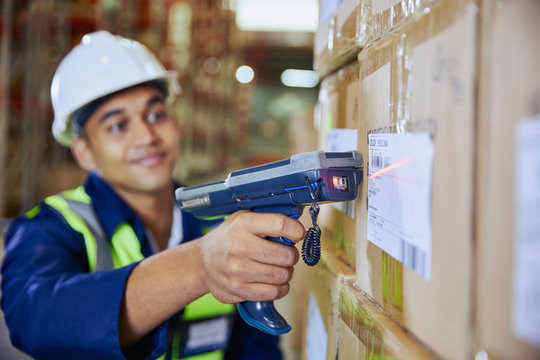 Worker with scanner scanning barcode on box in distribution warehouse
