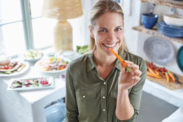 Portrait smiling woman eating carrot