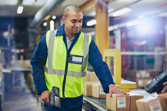 Worker with scanner scanning and processing boxes on conveyor belt in distribution warehouse