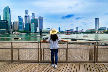 Young woman traveler with  hat traveling into singapore city downtown. Travelling in Singapore concept