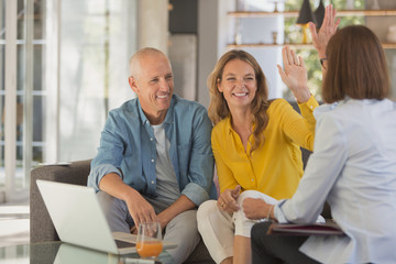 Happy couple high fiving financial advisor in living room