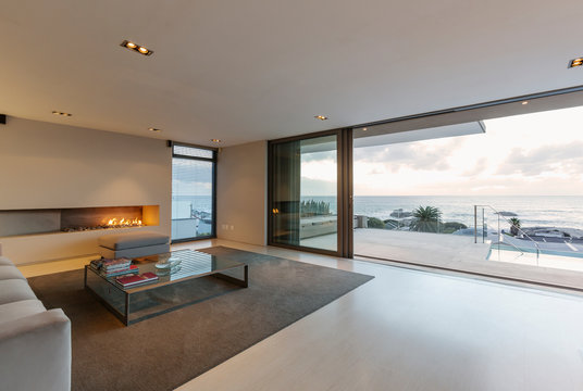 Modern, minimalist luxury living room with gas fireplace and patio doors open to ocean view and patio