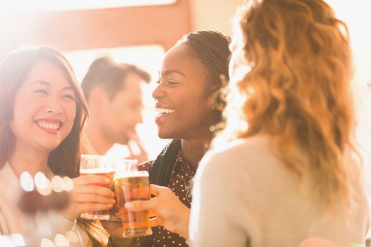 Smiling women friends toasting beer glasses in bar