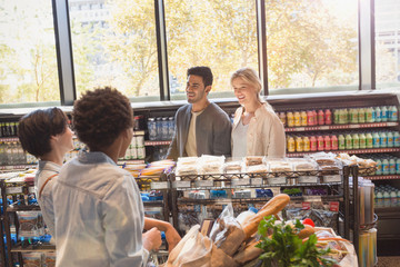 Young friends talking in grocery store market