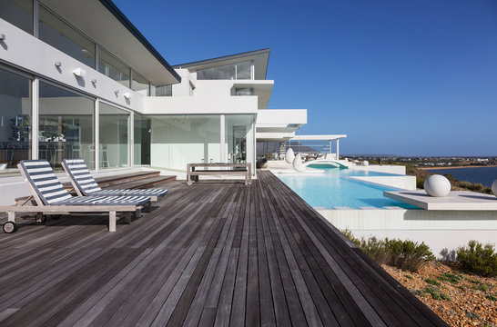 Sunny modern luxury home showcase exterior patio with infinity pool
