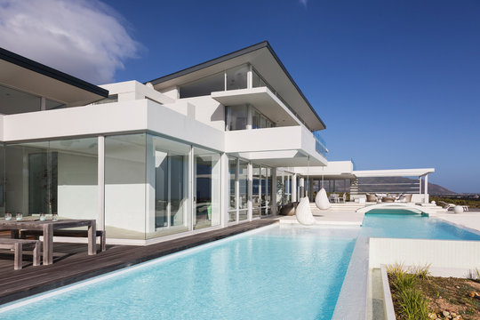 Sunny, tranquil modern luxury home showcase exterior with swimming pool