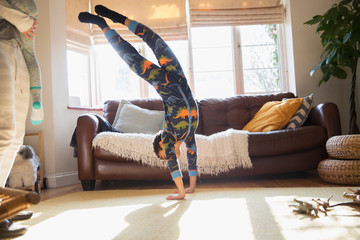 Playful boy in pajamas doing handstand in living room