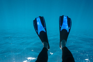 Personal perspective woman with flippers snorkeling underwater