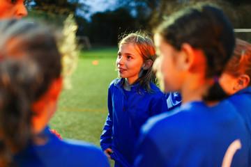Attentive girls soccer team listening to coach