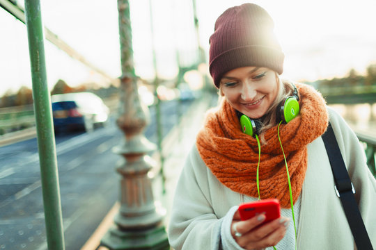 Young woman in stocking cap and scarf texting with smart phone