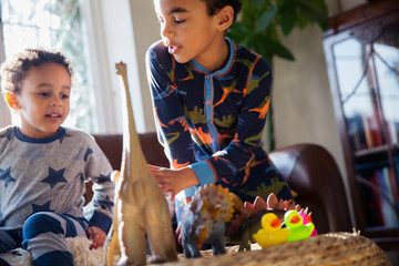 Brothers in pajamas playing with dinosaur toys