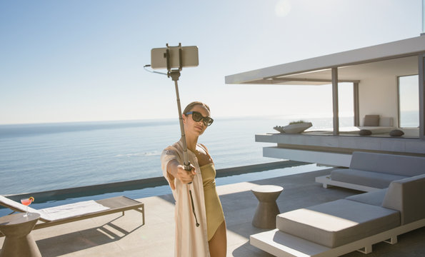 Woman in bathing suit taking selfie with selfie stick on modern, luxury home showcase exterior deck with ocean view