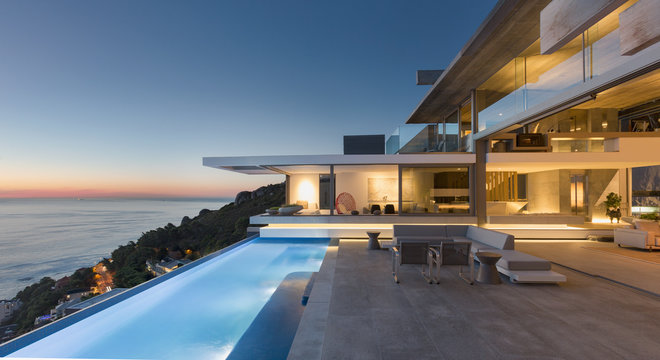 Illuminated modern, luxury home showcase exterior patio with lap pool and ocean view at twilight