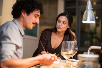 Couple eating dinner with chopsticks and drinking white wine at home