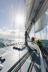 Woman at bow of sailboat on sunny ocean, Vava'u, Tonga, Pacific Ocean,
