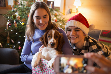 Brother and sister posing for photograph with dog in Christmas gift box