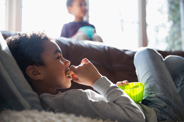 Boy eating snack and watching TV on sofa