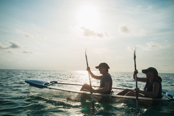 Women in clear bottom canoe on sunny ocean, Maldives, Indian Ocean