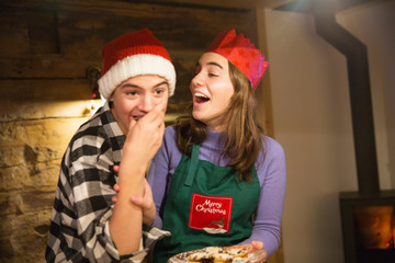 Playful brother and sister eating Christmas cookies