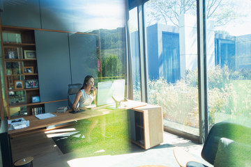 Businesswoman working at computer in sunny home office