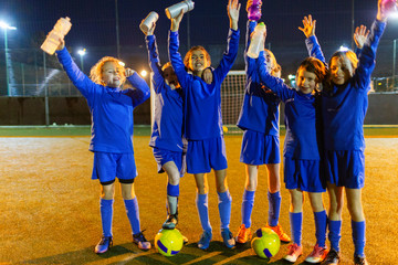 Portrait confident girls soccer team with water bottles cheering on field at night