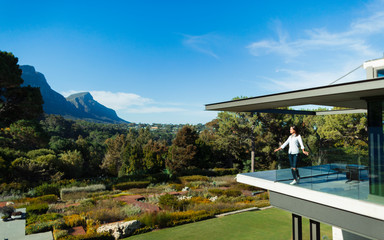Woman standing on sunny, modern luxury balcony overlooking garden and mountains, Cape Town, South Africa