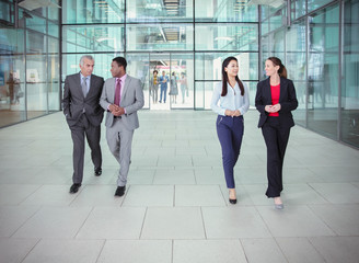 Business people walking and talking outside modern office building